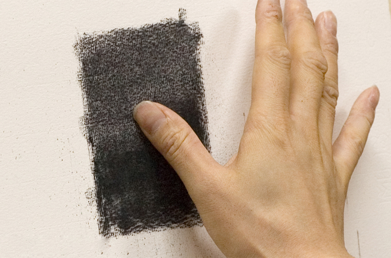 Pushing against the charcoal with a finger
