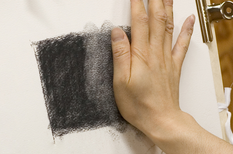 Pushing against the charcoal with the palm of the hand